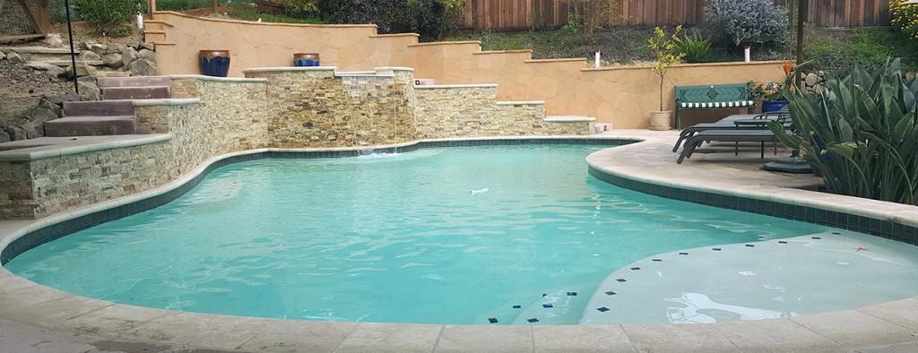 Custom swimming pool design with a waterfall from Aqua Dream Pools USA